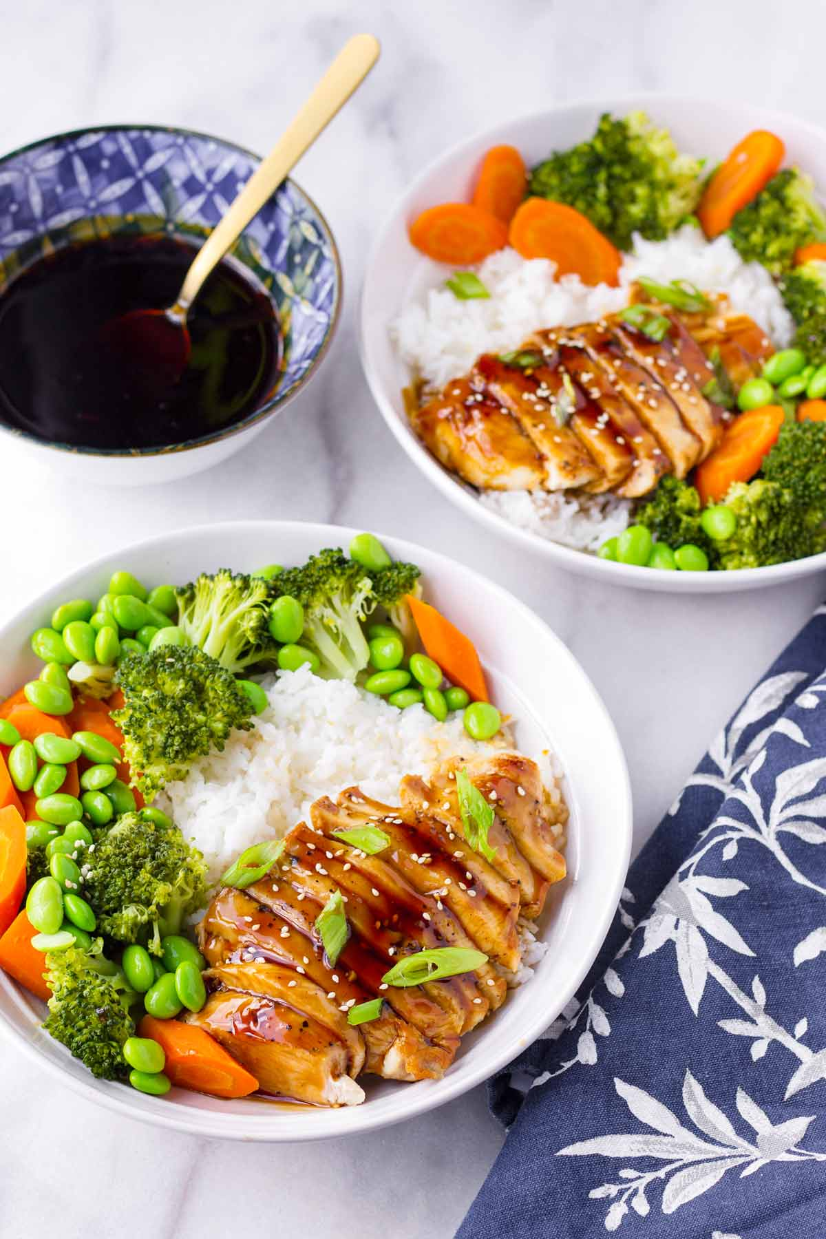 two chicken and veggie rice bowls with a side of teriyaki
