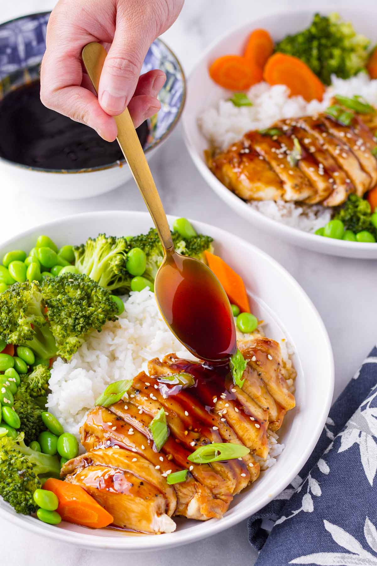 spooning teriyaki sauce over sliced chicken served with rice and veggies