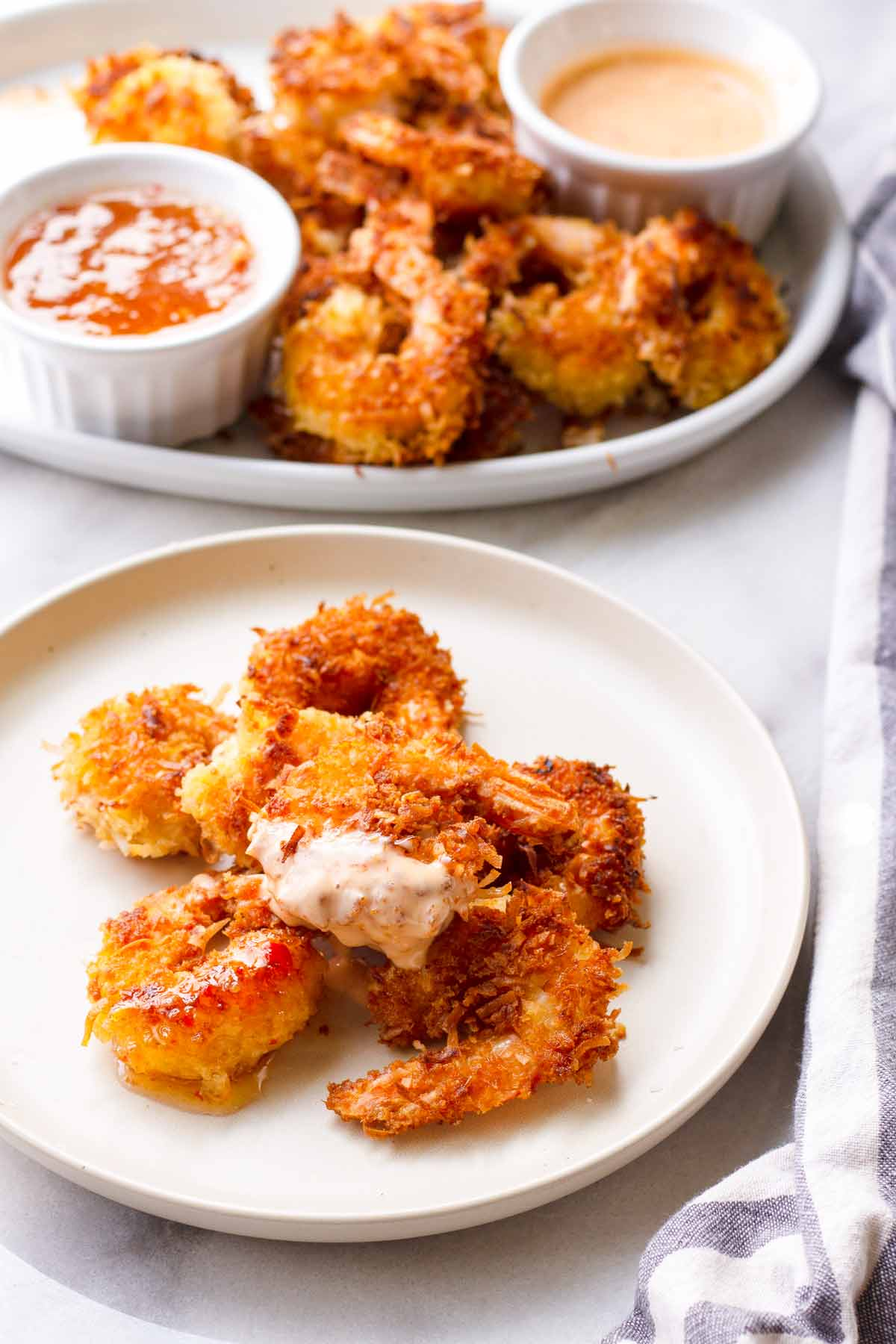 an individual plate with a serving of fried coconut shrimp plus more in the back