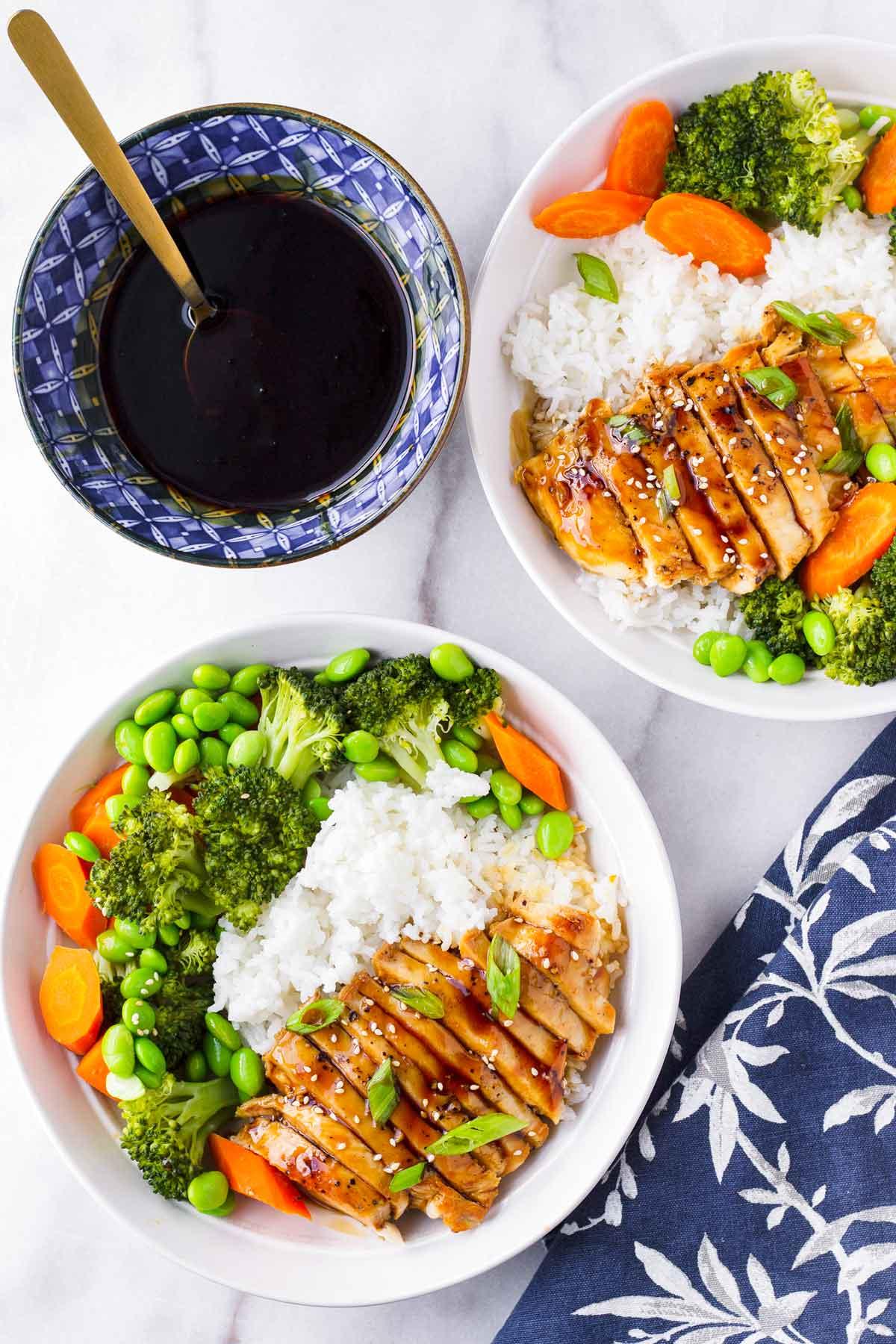 two prepared chicken teriyaki rice bowls with side of teriyaki