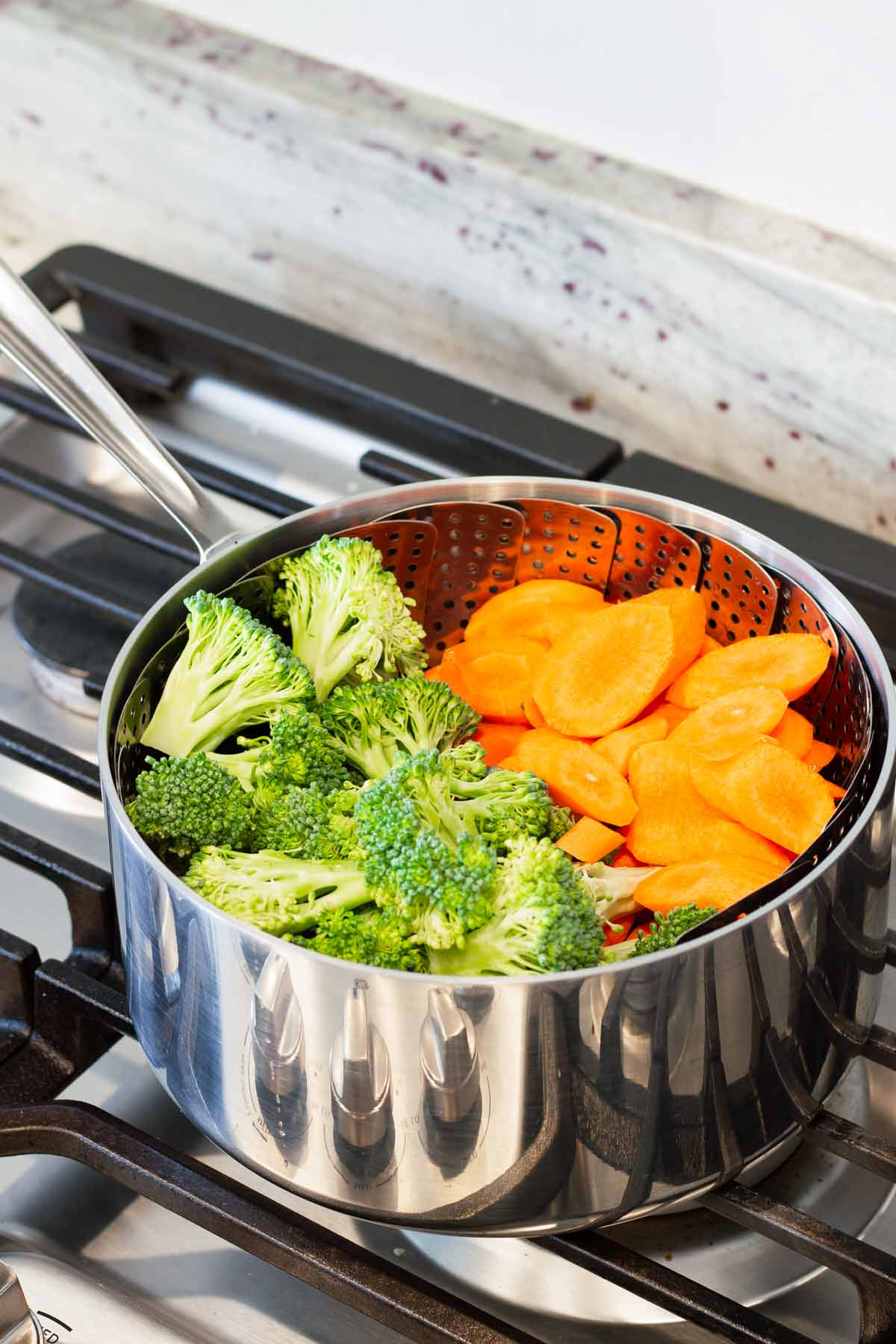 broccoli and carrots in a steamer basket