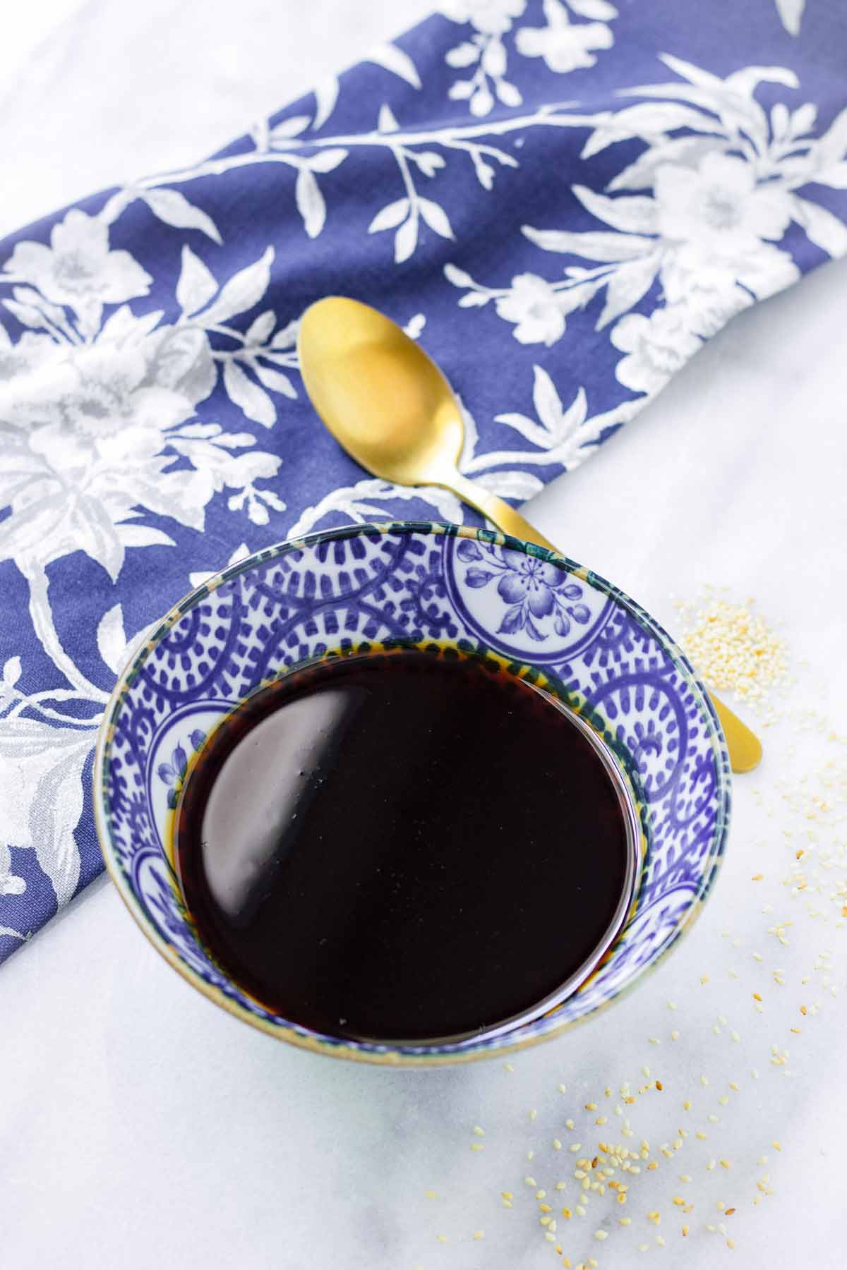 homemade teriyaki sauce in a blue bowl next to spoon and floral napkin
