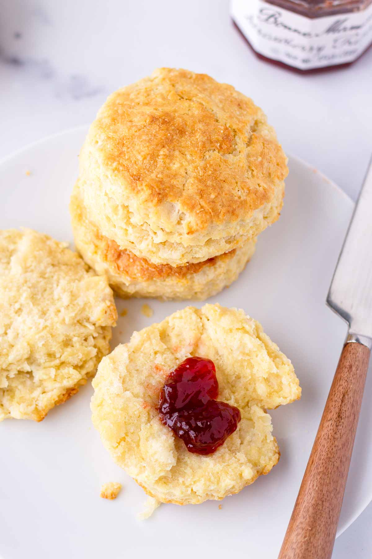 buttery biscuits with jam on a plate and a knife