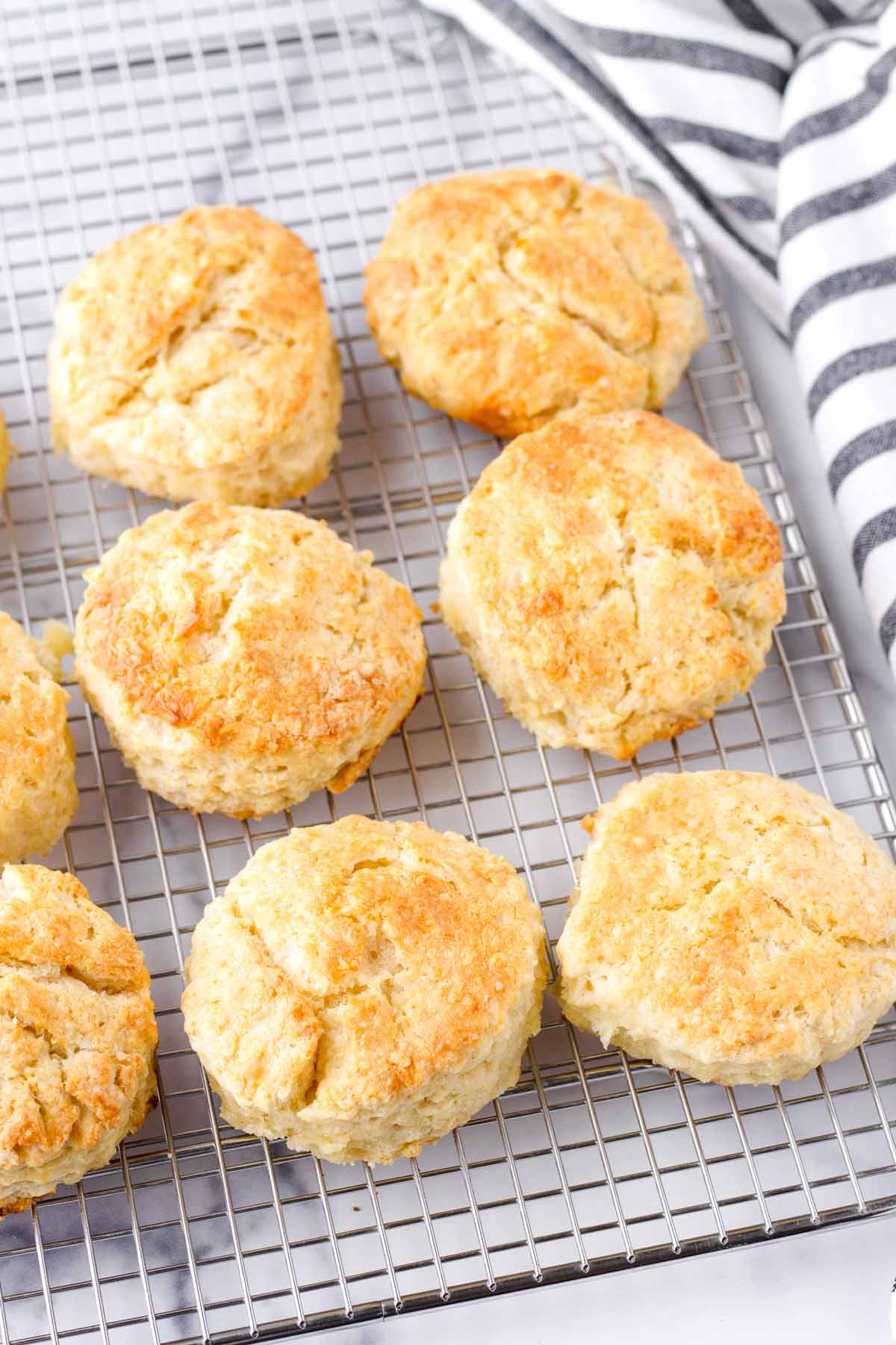 eight baked buttermilk biscuits on a cooling rack