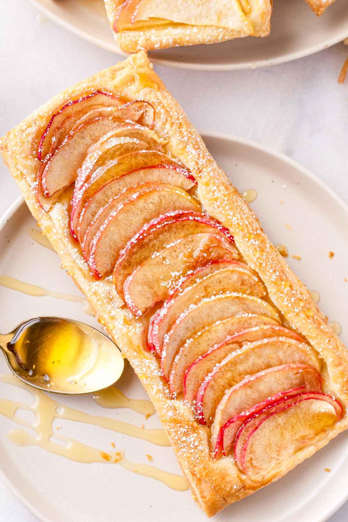 fruit flaky tarts next to a spoon with honey