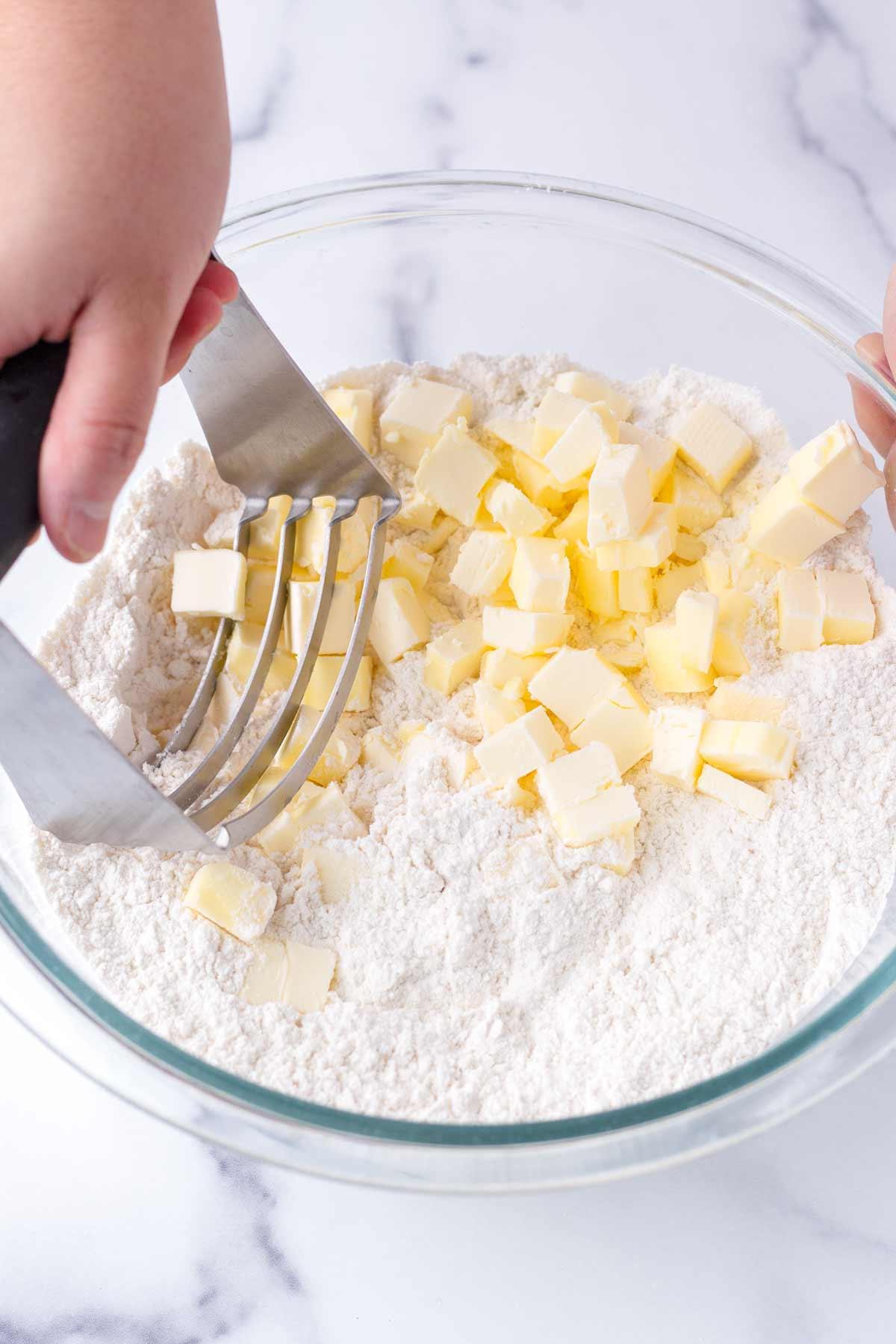 using a pastry cutter to work butter into flour