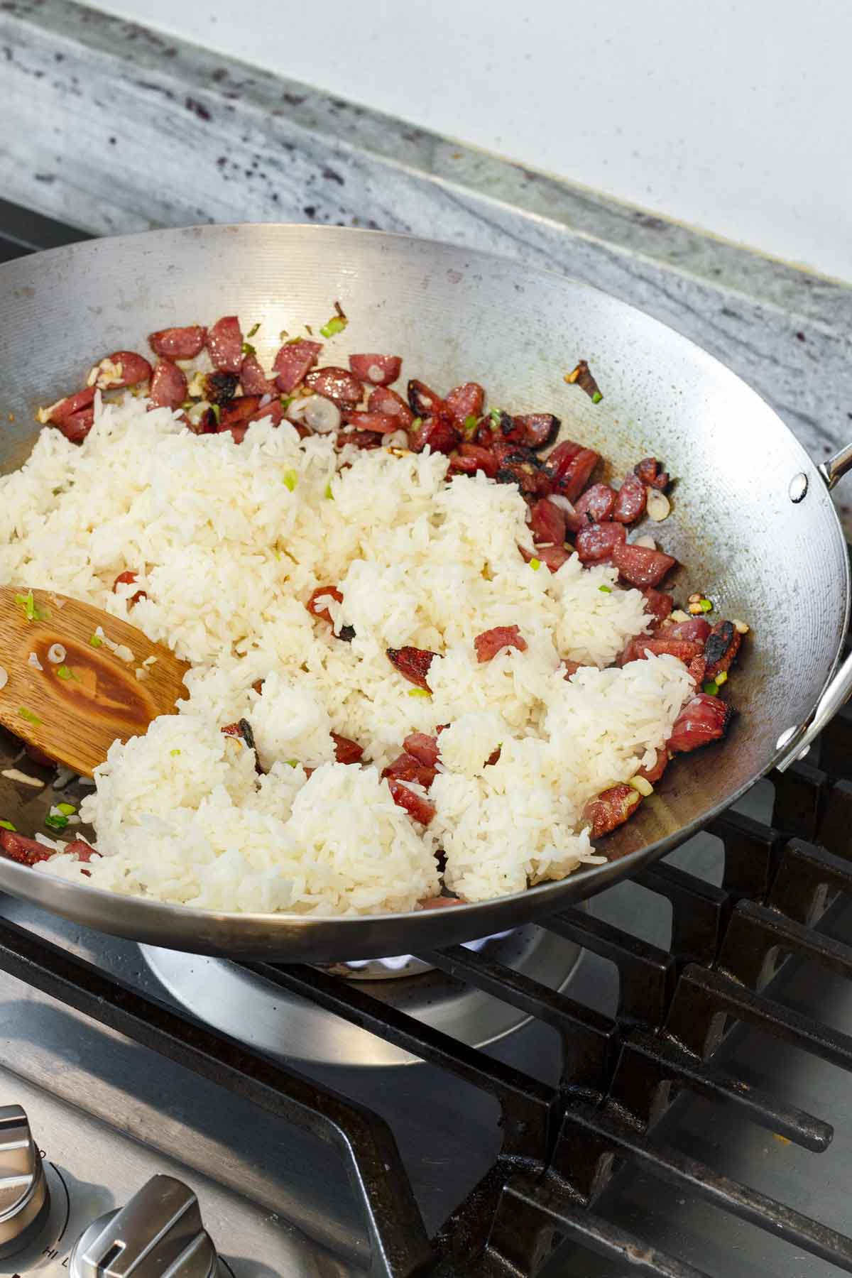 leftover cooked rice added to a wok with sausage