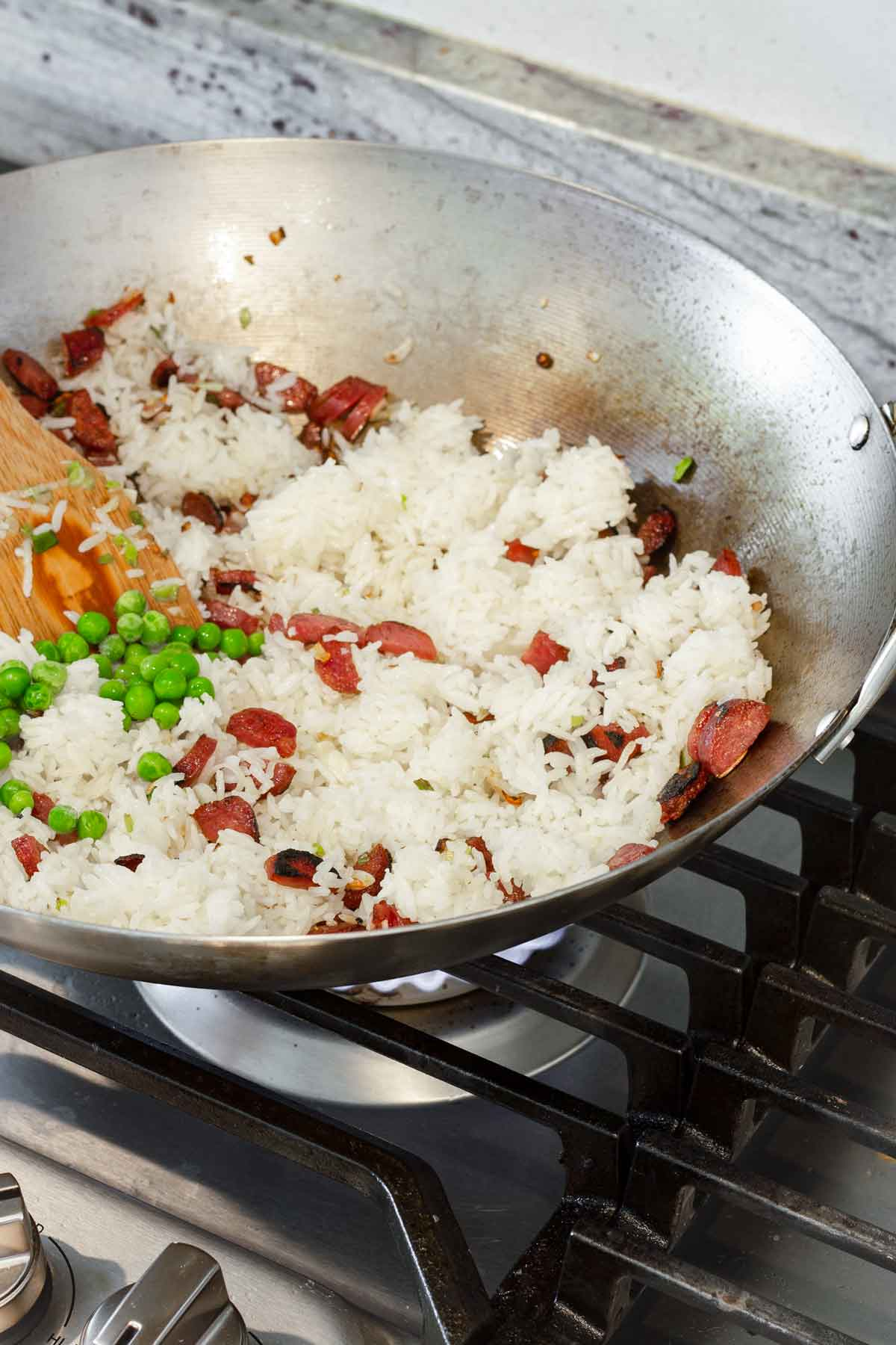 white rice added to a wok along with peas and chinese sausage