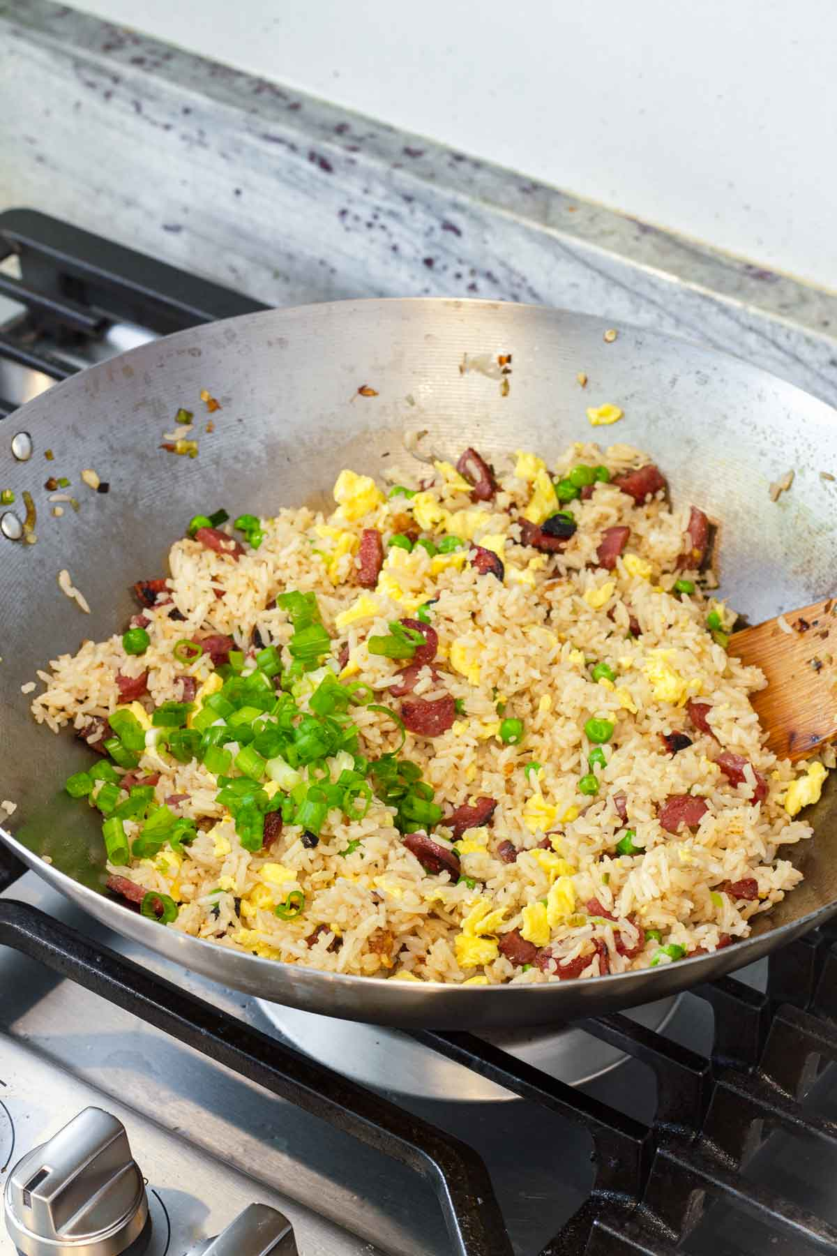 chinese sausage fried rice with scallions in a large wok