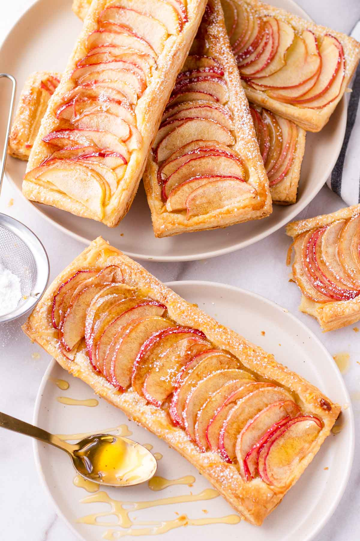 a baked puff pastry apple tart on plate with honey drizzles and a stack of more tarts
