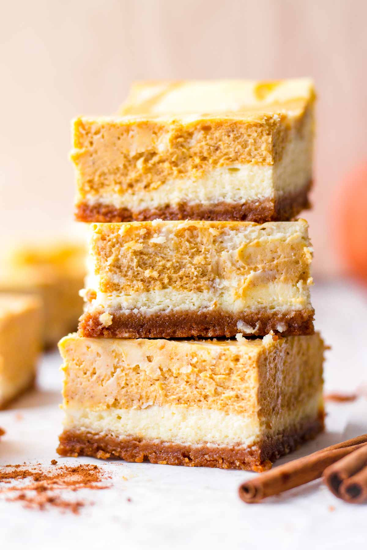 side view of three cheesecake bars stacked on top of each other