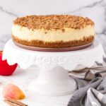 apple crisp cheesecake on a cake stand