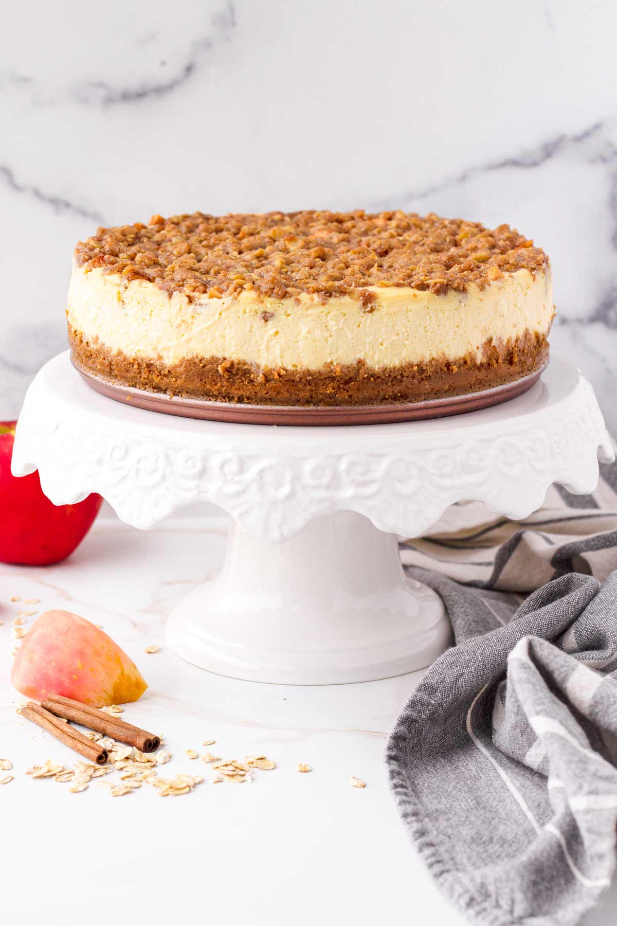 a 9 inch cheesecake topped with apples and oat crumble in a cake stand