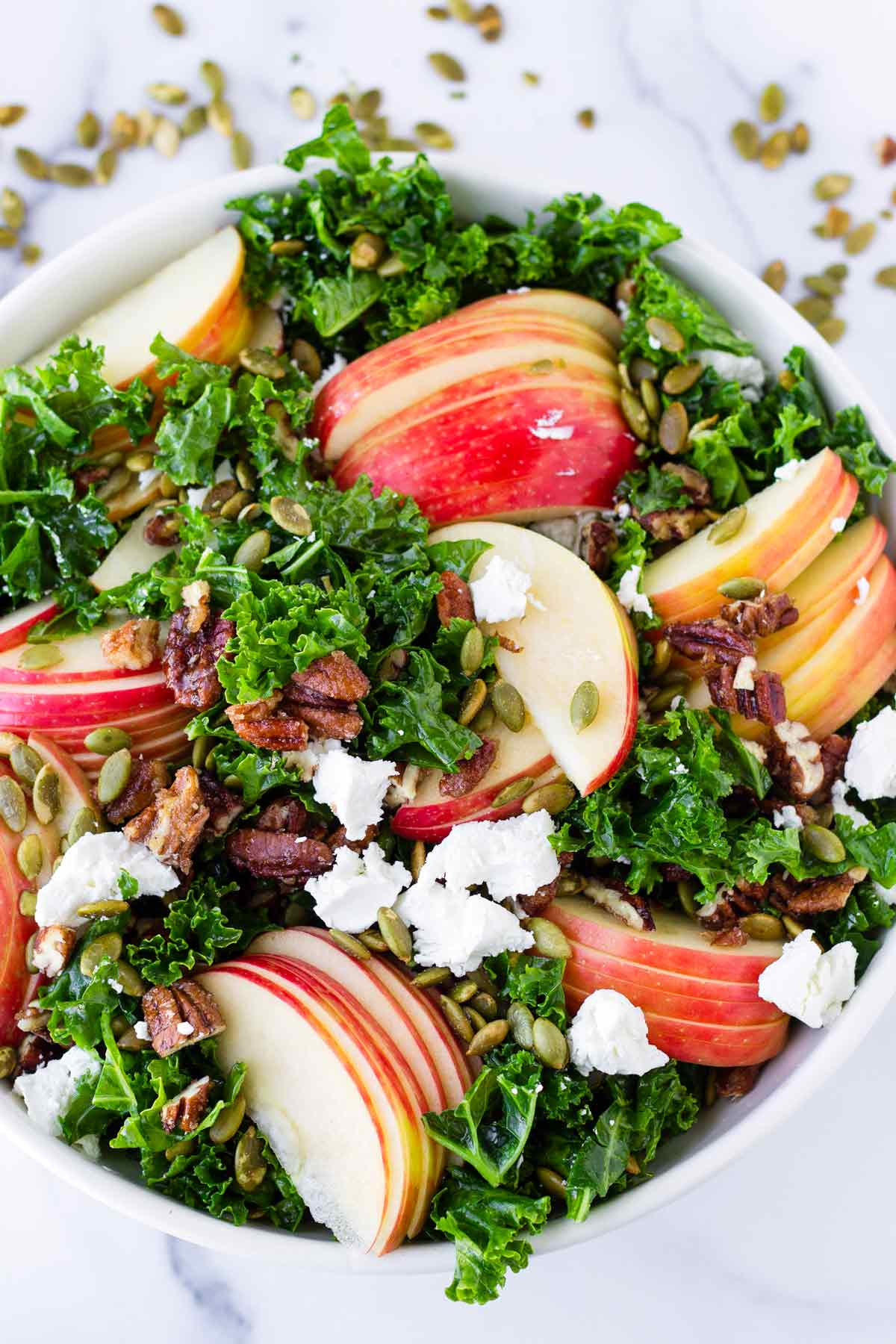 apple salad with kale, goat cheese, nuts, and pumpkin seeds