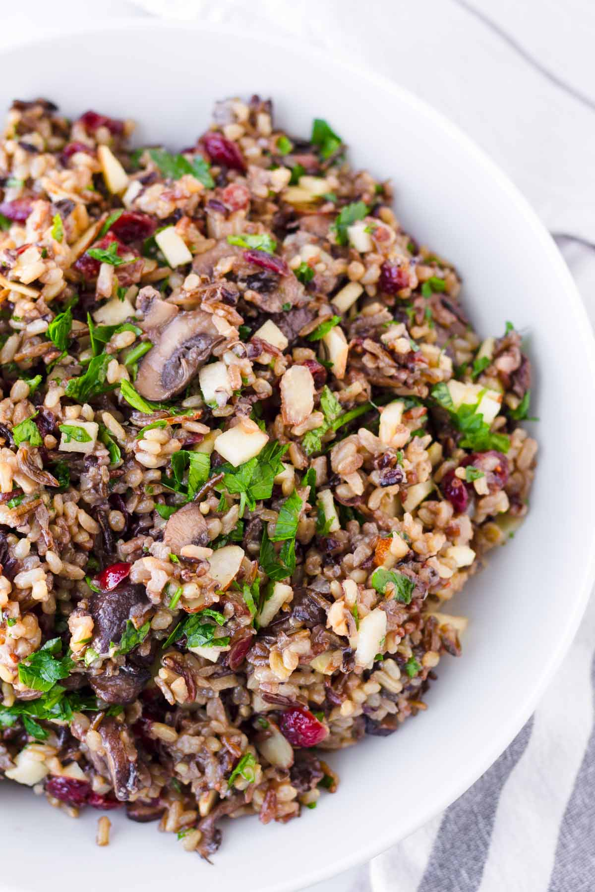 close up of garnished wild rice pilaf with mushrooms, apples, cranberries