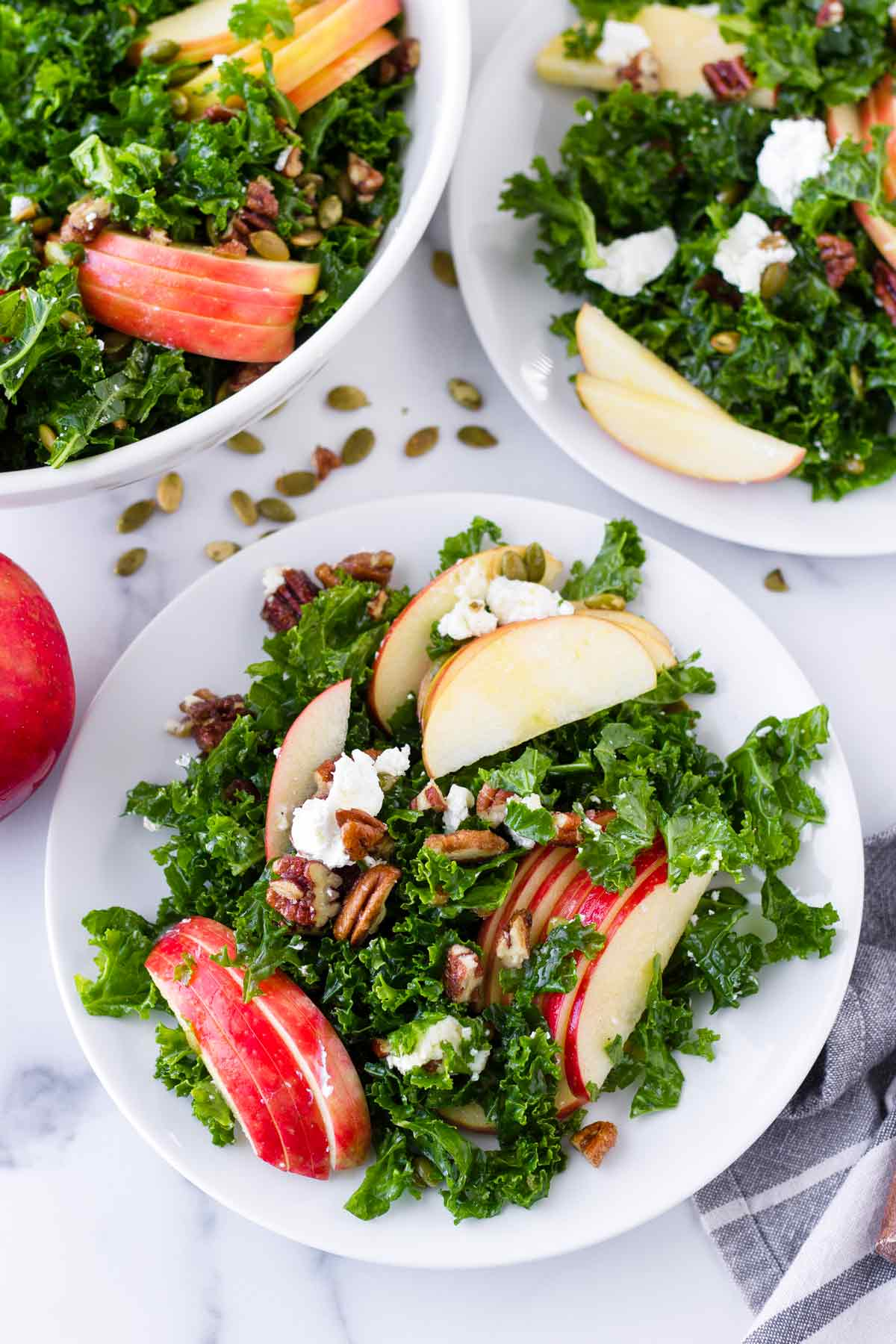 individual servings of kale and apple salad on plates