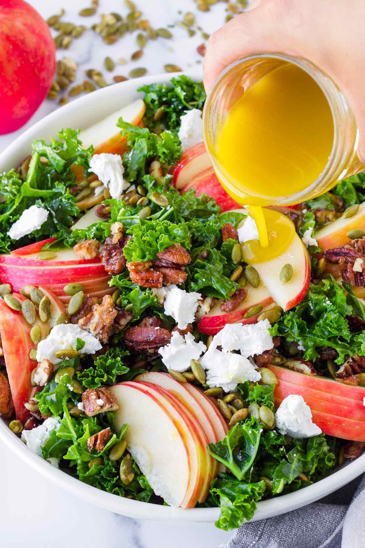 drizzling vinaigrette on top of prepared apple kale salad