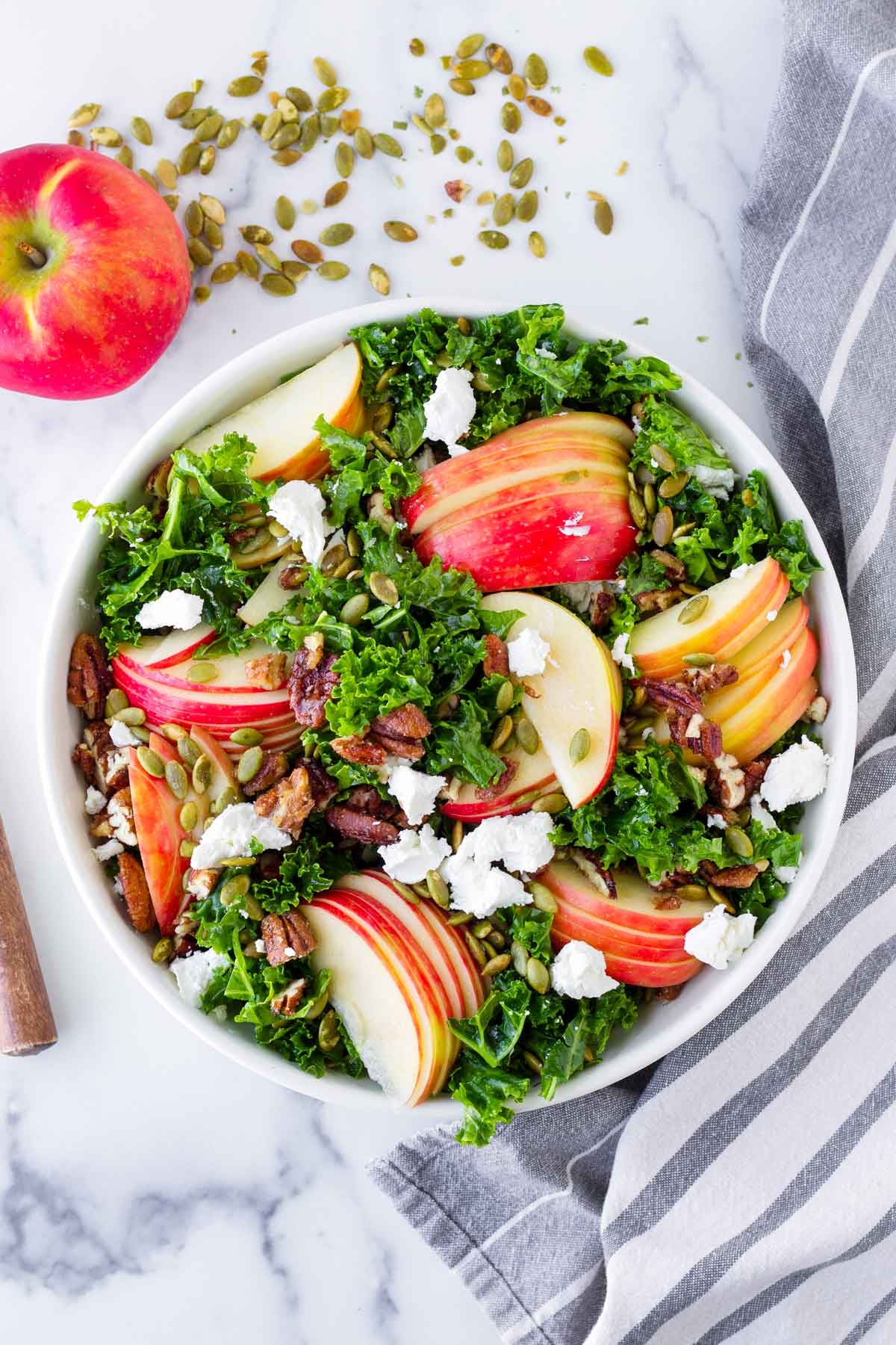 top view of a decorated apple kale salad next to napkin