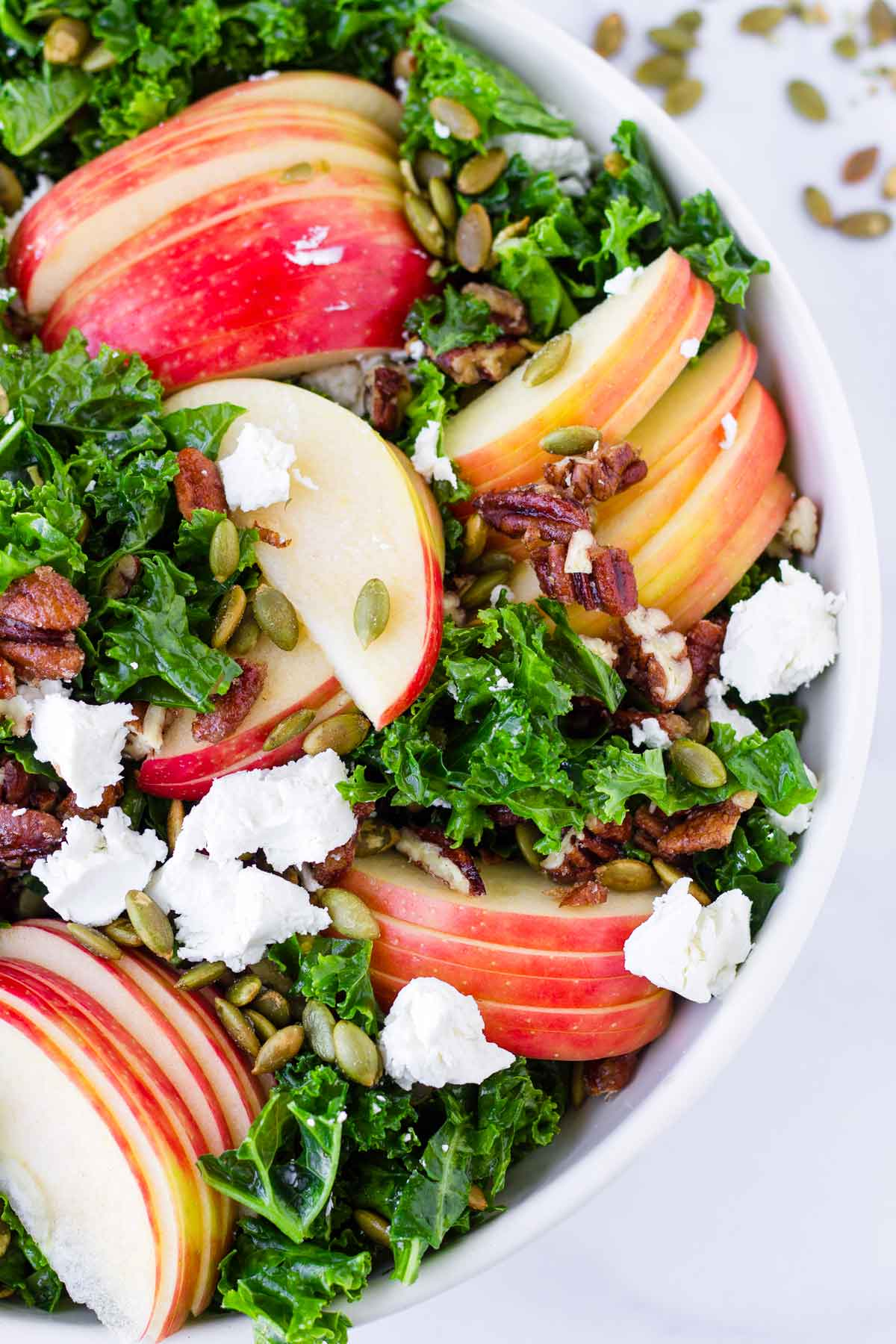 close up of bowl with sliced apples on top of kale, cheese, and nuts
