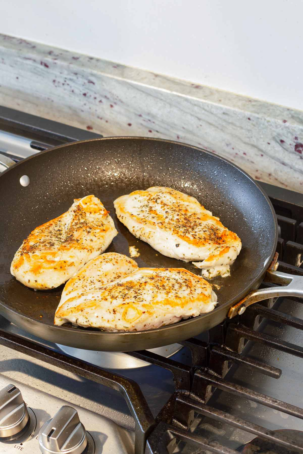 pan-searing chicken breasts on a skillet