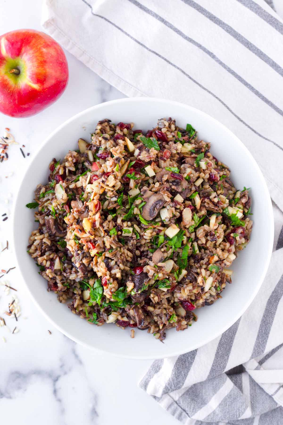 top view of wild mushroom pilaf in round bowl with apple